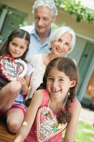 Germany, Bavaria, Grandparents with granddaughter holding gingerbread, smiling