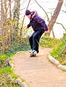 Worried young guy skateboarding down a path