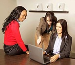Four young business women looking at laptop, Johannesburg, South Africa