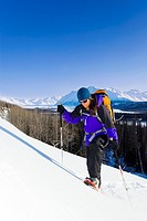 A Woman enjoys a sunny day of snowshoeing in the Talkeetna Mountains near the Matanuska Glacier. Winter in Southcentral Alaska
