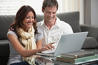 Young smiling couple using laptop