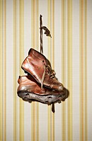 Pair of old shoes hanging on striped background