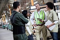 Manual workers talking in warehouse