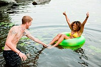 Couple playing on inflatable ring on lake (thumbnail)