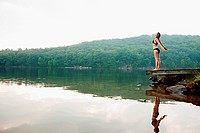 Young woman standing on pier over lake