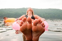 Close up of young woman floating in lake