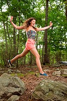 Young Hispanic woman jumping over stones in forest