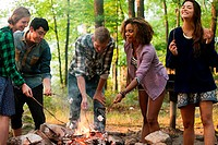 Friends cooking over campfire in forest