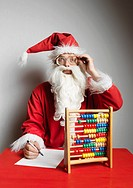 Man in Santa Claus suit using abacus