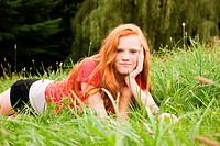 Teenage girl lying down on the grass chilling out