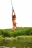 Teenage girl swinging on a rope over a lake