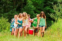 Teenagers carrying a hamper in the countryside