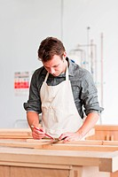 Carpenter using mitre in workshop (thumbnail)