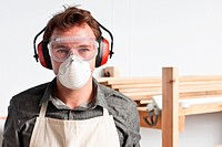 Carpenter wearing dust mask and ear defenders, portrait (thumbnail)