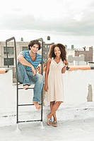 Portrait of young couple on roof of apartment building
