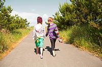 Girls carrying skateboards along rural road