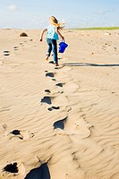 Girl running through sand at beach