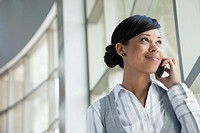Young businesswoman talking on cell phone by window