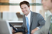 Portrait of smiling businessman at desk