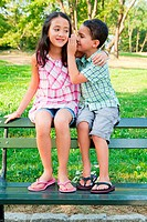 Boy whispering secrets to girl on park bench