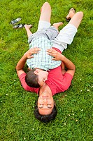 Father lying on grass with son