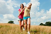 Young women running through a field together