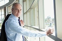 Portrait of mature businessman standing near window