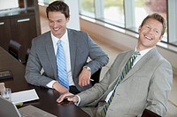 Two businessmen smiling at desk