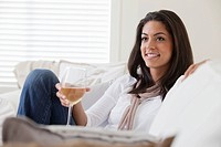 Woman sitting on sofa having glass of white wine (thumbnail)