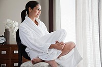 Woman wearing bathrobe sitting on chair and smiling (thumbnail)