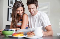 Young couple having breakfast and reading newspaper