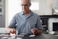 Middle-aged man playing solitaire (thumbnail)