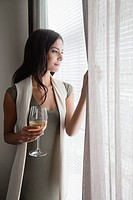 Young woman holding wineglass and looking through window