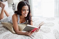 Young woman lying on bed and reading book