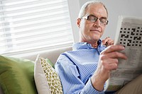 Smiling middle-aged man reading newspaper on sofa (thumbnail)