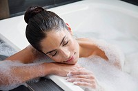 Young woman relaxing in bathtub (thumbnail)