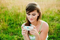 Young woman looking at a hand held device in a field