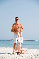 Father holding son in a headstand position on a beach