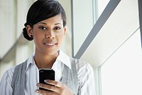 Portrait of smiling young businesswoman using cell phone