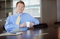 Businessman sitting at desk with coffee