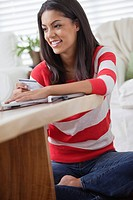 Young woman sitting in living room (thumbnail)