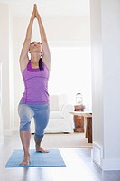 Mid adult woman practicing yoga at home