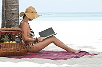 Woman Reading Electronic Book on Beach, Aruba