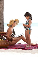 Mother and Daughter Touching Hands on Beach Blanket, Aruba