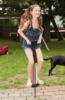 Girl playing on pogo stick in backyard