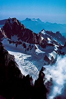 An aerial view of jagged peaks and slow moving glaciers of the Alps.
