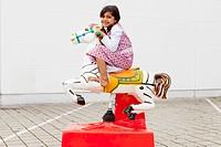 Girl riding mechanical horse outdoors