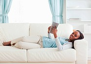 Young woman lying on couch reading a book