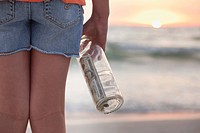 USA, Florida, St. Petersburg, Girl 10_11 holding bottle with money on beach, mid section