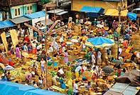 An open air market with locals selling vegetables and household items.